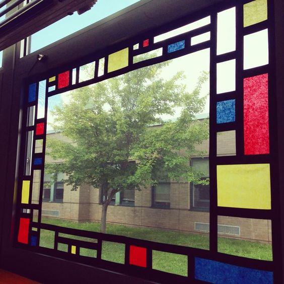Piet Mondrian inspired window art. Blocks of tissue paper stuck down with lines of black electrical tape.