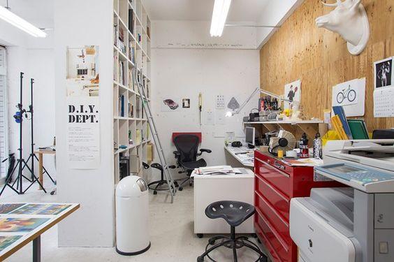 デスクワークのスペースは、天井までの大きな本棚でゆるやかにパーティションされている。木目の構造合板の向こう側がカスタムペイントするスペース。