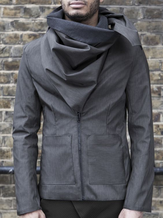 The Utilitarian Jacket   Reversible: Waterproof fabric + Dark grey wool suiting Draped collar behaving like a scarf to protect from the elements. It gets tucked into an opening in the scarf itself in order to keep it in place Reversible zip as front fastening and in cuffs Reversible pockets Slim fit by Scilla Morelli