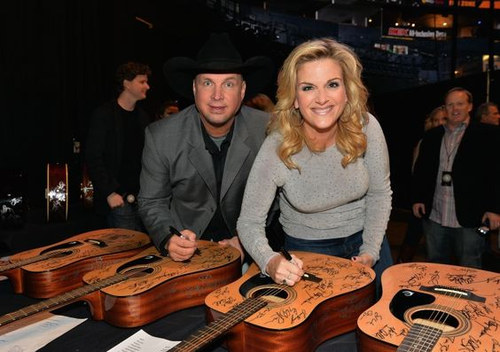 A couple that signs autographs together, stays together. Garth Brooks and Trisha Yearwood add their John Hancocks to guitars at the Playin' Possum! The Final No Show tribute To George Jones on Nov. 22 in Nashville, Tenn.