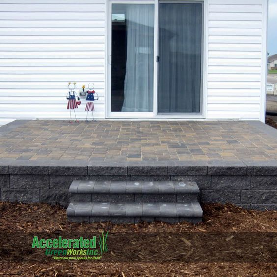 raised paver patio with steps to the landscaping versa