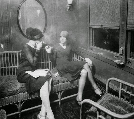 Flappers smoking cigarettes in a train car, ca. 1920s