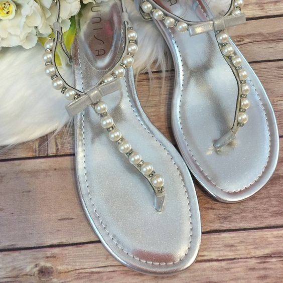 Silver Pearl Bow Sandals Size 9.5 NEW Brand new. They are a size 9.5 and I'm a 9 but I thought they'd fit. If my foot wasn't so Narrow they would have worked. But my foot is so narrow it was work just walking around the house to hold them on. Unisa Shoes Sandals