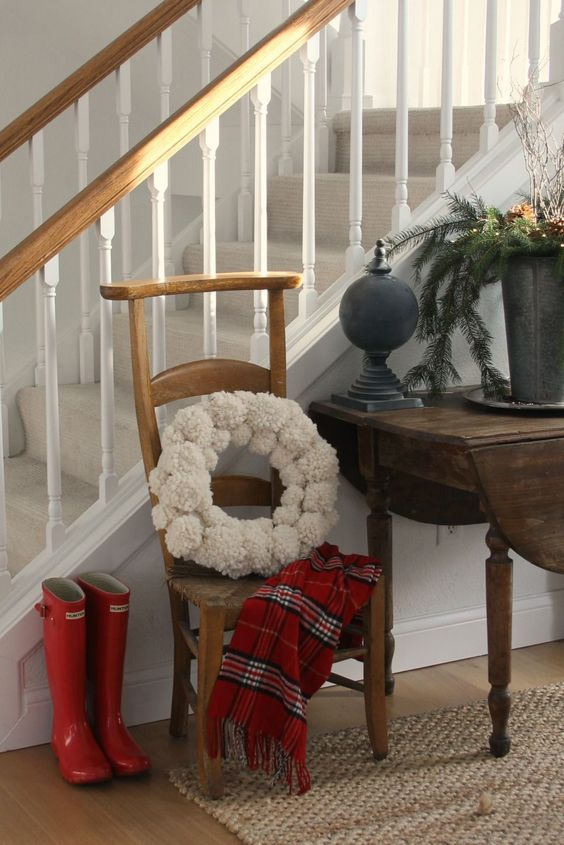 Christmas decor in a country house entry with red boots, red plaid scarf, wooly pom pom wreath, and fresh greenery. #hellolovelystudio #christmasdecor #redboots #pompomwreath