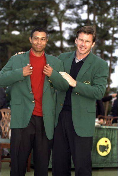 Nick Faldo gives Tiger Woods the green jacket in 1997. | Golf