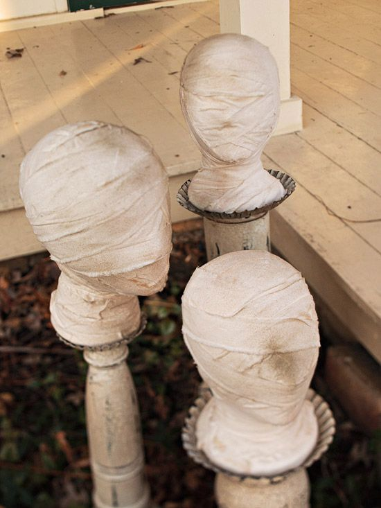 """Mummy heads> """"To make them, decoupage head forms with strips of white muslin (a great use for old sheets) and then scuff them up by rolling them around in the yard. Hot-glue the heads to wood posts and add bits of raffia."""""""