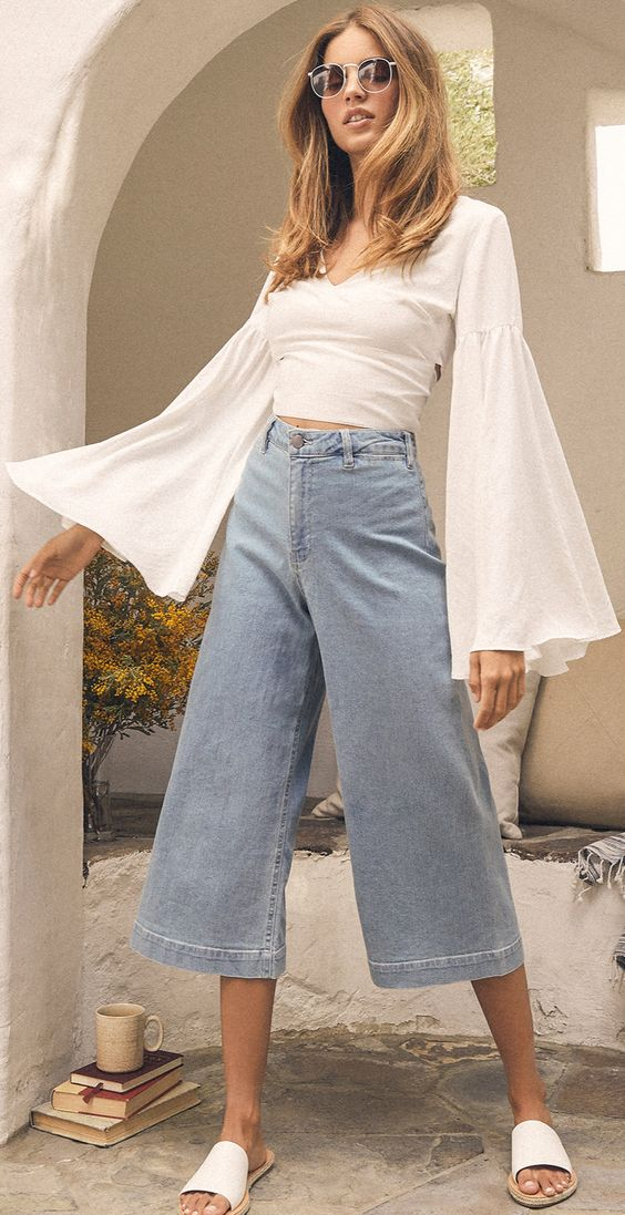 Step into summer in style in light wash denim culottes and a breezy white top. The sailor-style pants are high-waisted with a stretchy fit. The lightweight white bell sleeve crop top is the perfect match for a retro-inspired outfit. Pair with white slide sandals, round sunglasses, and you are ready for a day at the park. #lovelulus