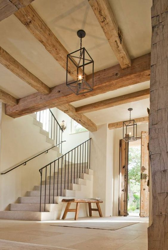 French farmhouse interior design inspiration flows from this magnificent architecturally stunning entry with natural rustic antique beams, double doors, stone steps, and delicate wrought iron railing. The palette is quiet, and the mood is naturally elegant.#frenchfarmhouse #frenchcountry #entry #interiordesign #rusticdecor #beams #staircase #homedesign #european