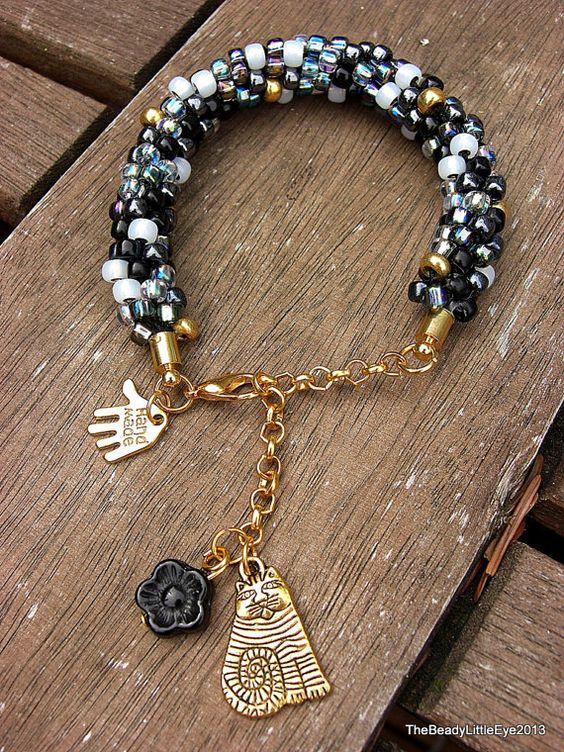 Tabby Chic, unieke handgemaakte armband met zwarte en witte glaskralen en een kattenbedel. op Etsy, 12,50€