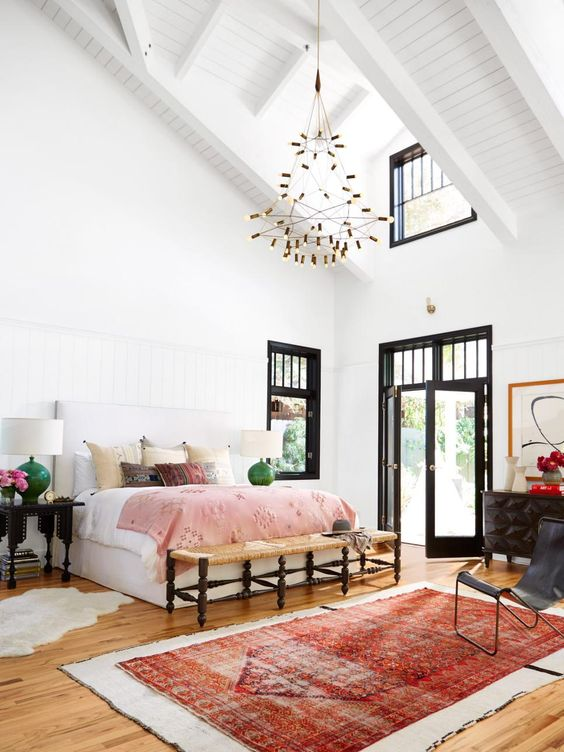 Light-filled bedroom features a high vaulted ceiling and bold black