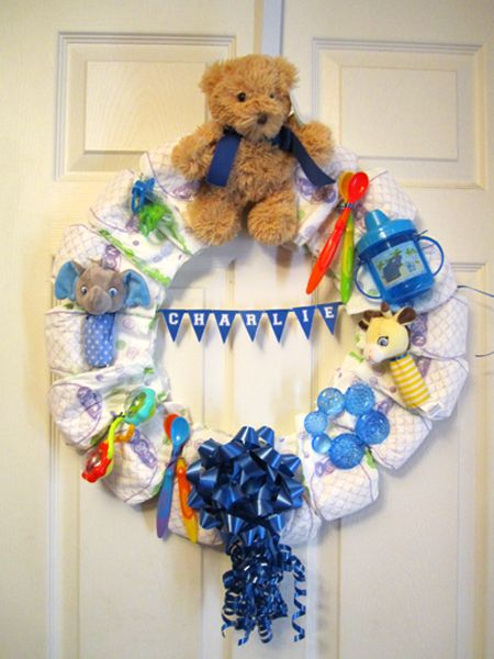 Diaper wreath - perfect for the hospital room door or a welcome home present. And the toys attached are gifts for the baby!