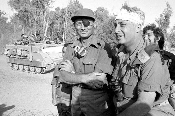In October 1973, future Israeli Prime Minister Ariel Sharon helped turn the tide of the fourth Arab-Israeli war after a surprise attack by Egypt and Syria, eventually encircling the Egyptian Third Army. Mr. Sharon (right), recovering from a head injury, stands with Israeli Defense Minister Moshe Dayan on the western side of the Suez Canal
