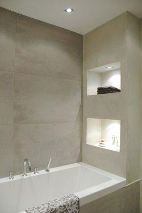 Een nis met verlichting in je badkamer maakt het geheel optisch groter. Prachtig contrast tussen de tegels en het witte sanitair.