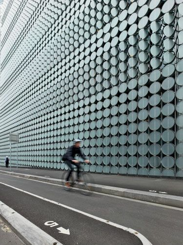 RMIT Design Hub : Sean Godsell Architects : Melbourne :   The facades are divided into 774 panels, each three discs wide and seven discs tall. Within each panel, the top three discs are fixed; the bottom four, which are in the occupants' line of sight, are operable.