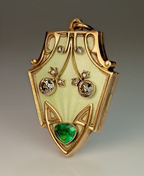 A Superb Russian Art Nouveau Antique Locket, St. Petersburg, 1904-1908. The front of the locket is covered with a very fine pale golden green guilloche enamel and applied with a pair of stylized diamond-set cherries within an ornate Art Nouveau gold frame. The lower tip of the shield-shaped locket is embellished with an emerald of a nice color.