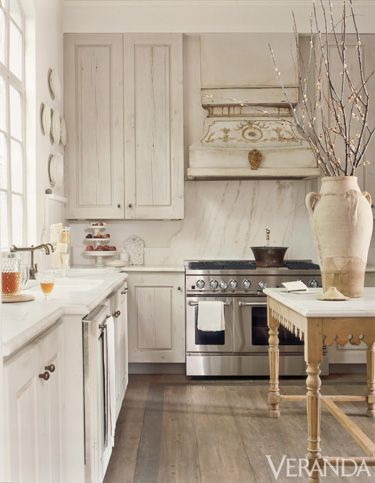Cabinets from reclaimed pine planks add to the subtle palette in this kitchen.