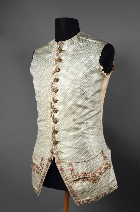 Waistcoat of a court suit, France, Louis XVI. Silk brocade woven in light green, cream and silver lamé, embroidered with garlands of flowers along the edges and pocket flaps, embroidered buttons.