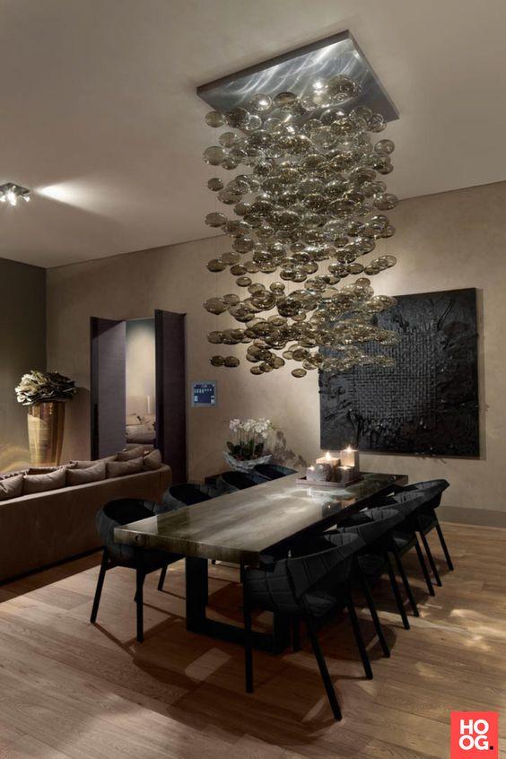 Houten eettafel met luxe stoelen en design verlichting eetkamer