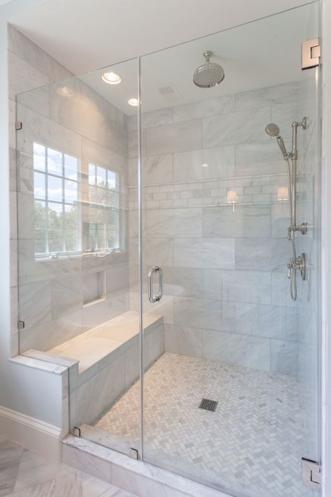 Walk in glass shower with built in shower seat and marble shower walls in master bathroom of custom home by BCN Homes in Arlington, Virginia