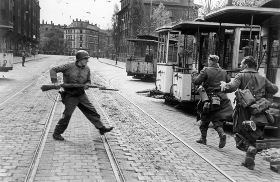 April 18th, 1945. Immediately after an American soldier had been killed, his comrades went down to the street to capture the snipers who had shot him.