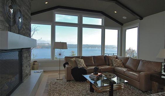 Washington waterfront living room, large tan leather l-shaped couch, stone fireplace, modern grey mantle and raised hearth, glass coffee table, white wood window trimmings, dark wood ceiling beams, grey interior