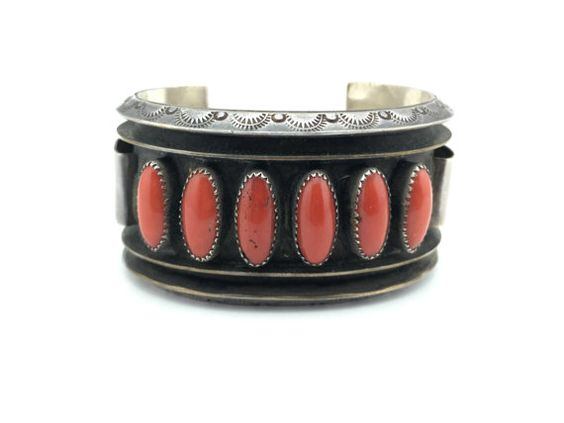 This is a fantastic vintage cuff made of sterling silver with hand stamped markings, and six pieces of coral prominently displayed on the face. The coral pieces are all in great shape and remain firmly in place. The silver has a dark patina and the piece is overall ready to wear.  Markings: Alice Sam Content: Coral and sterling silver Size: 4 1/2 + 1 1/5 gap Width: 1 2/5 Weight (grams): 90.8  Please feel free to reach out if you have any questions or would like additional photos. Were…