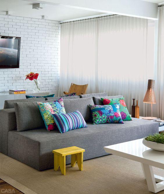 O sofá cinza entra em harmonia com o tapete e as cortinas, a decoração fica por conta do colorido das almofadas e o banquinho amarelo que dão um up no visual e transformam o ambiente numa sala moderna e cheia de estilo.: