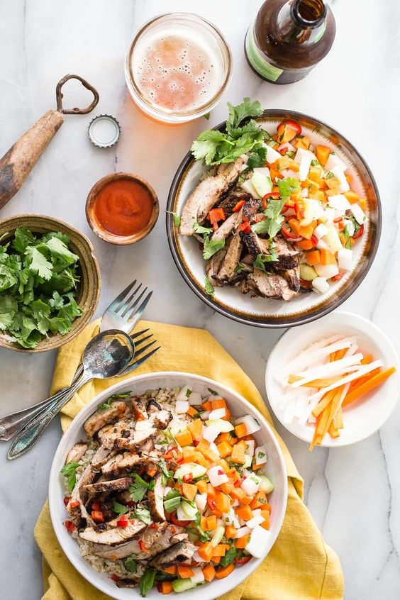 Tasty chicken marinated in five spice and served with brown rice and pickled veggies. This banh mi style chicken rice bowl is awesome!: