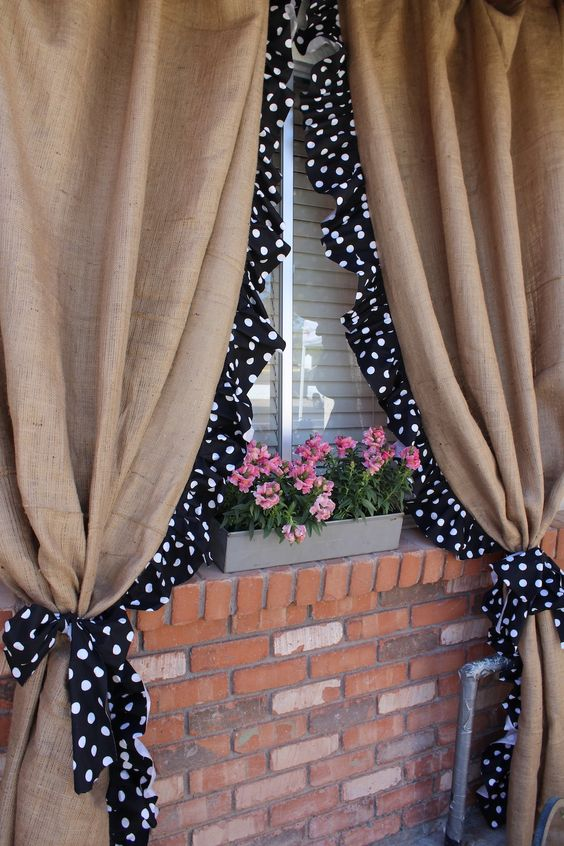 Burlap curtains with polka dot trim on an exterior porch window.