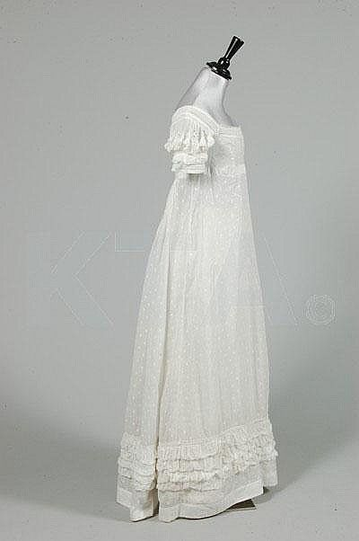 A sprigged muslin day dress, circa 1825, embroidered overall with minute leaves and flowerheads, puffed cutwork sleeves edged in ruffles of muslin, similar broad ruched band to hem.: