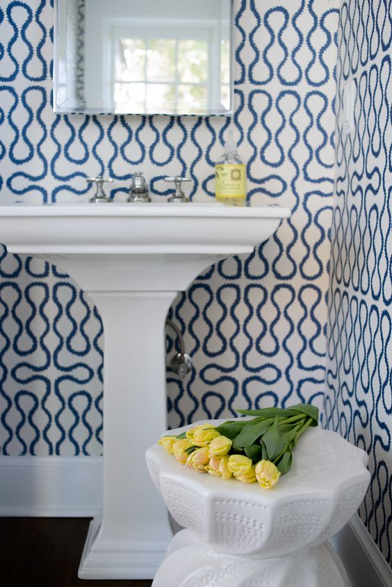 Whimsical blue and white bold wallpaper in a bathroom with pedestal sink. Blue and White Classic Decor Inspiration: Ella Scott Design. #blueandwhite #classicdecor #interiordesignideas #interiordesigninspiration #traditionalstyle #bathroomdesign #wallpaper
