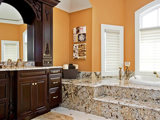 The golden poppy walls play off the warm, neutral marble bathtub surround and rich chocolate vanity by Vanessa DeLeon.