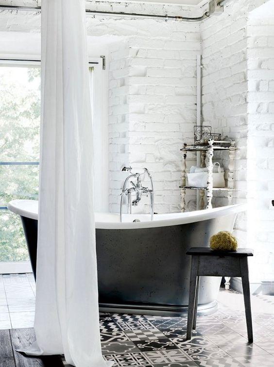 murs de brique blanche et une baignoire îlot dans la salle de bains