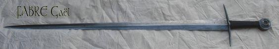 Epée de guerre à partir du XIVème siècle.  Epée entièrement forgée en acier feuilleté à lecture damassée. Lame de 80 cm de longueur, de 5 cm de largeur et de 7 mm d'épaisseur au talon.Emouture à pans concaves.    Pommeau à roue à pans concave et moyeux évidé.  L'ensemble est feuilleté à plus de 600 couches d'acier.  Fusée en chêne recouvert de cuir bouilli.  Poids: environ 1100 grammes