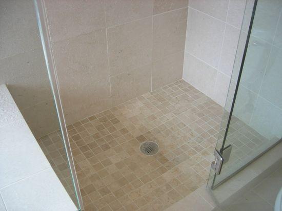 Tumbled marble tiles on shower floor/  frameless glass shower and Italian crema tiles shower surround.