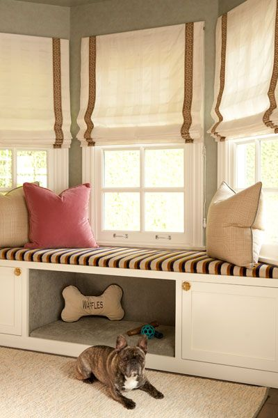 This pup loves lounging outside of his custom dog bed!  Briliant idea to build it in to an existing window seat!  Roman shades with greek key trim and plush pillows finish the look.  #jfdesigns #jennfeldmandesigns