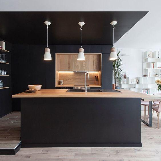 Cuisine noire avec plan de travail en bois clair. Un design très moderne et épuré.