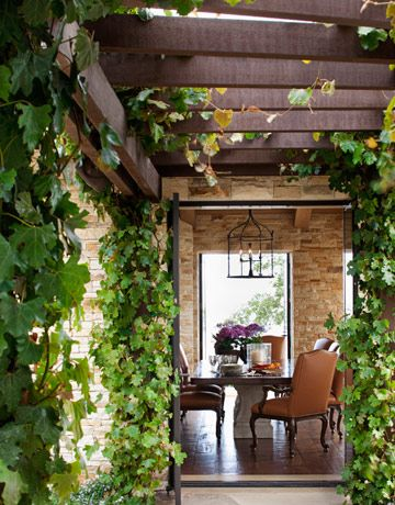 Ivy via housebeautiful.com-love the beams with the brick against the greenery
