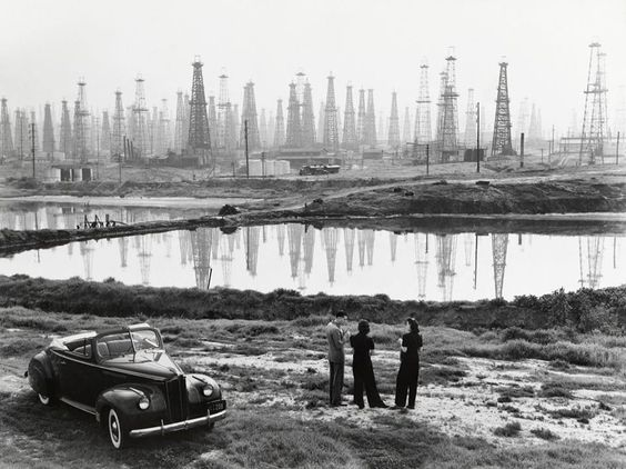 A forest of oil derricks makes a ghostly backdrop for a conversation in Signal Hill, California, in 1941. The city is located north of Long Beach in Los Angeles County. The complex geology of the L.A. Basin caused massive amounts of oil to be trapped beneath the city, which fed a booming oil industry at the turn of the century. At their peak, the wells at Signal Hill led California oil production.  Photograph by B. Anthony Stewart, National Geographic