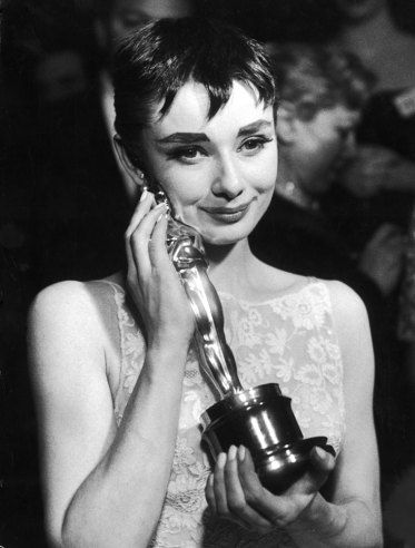 Audrey Hepburn, the actress who starred in Sabrina, rocks a beautiful lace-patterned dress while holding an Oscar that she had just received because of her wonderful performance in the movie 'Roman Holiday'. This photograph was taken in 1954 (http://life.time.com/movies/academy-award-winners-classic-hollywood-stars-and-their-oscars/photo/6/).