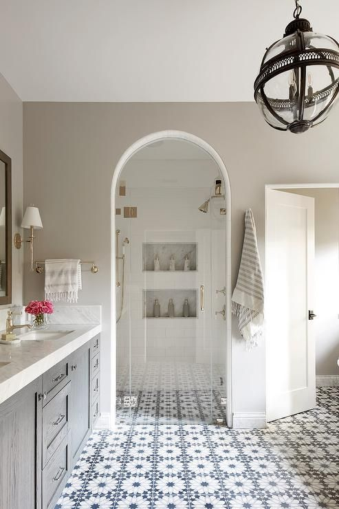 Transitional Master Bathroom Features An Arched Shower Glass Door With Brass Hardware Viewing Into Bathrooms Remodel Spanish Style Bathrooms Bathroom Interior