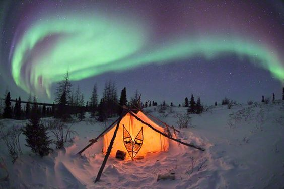 An illuminated tent sits beneath the Northern lights in Hudson Bay, Canada.  Photographer: Thomas Kokta