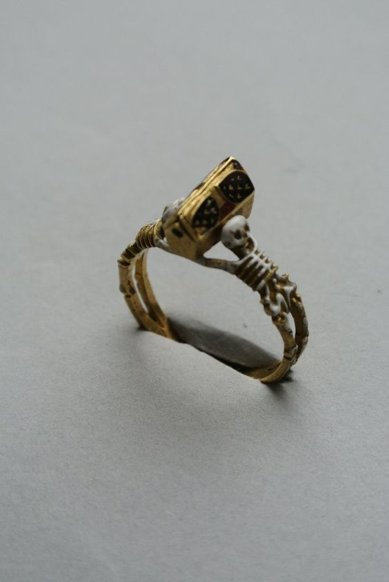 Mourning-ring; enamelled gold, the hoop enamelled white, in the form of  two skeletons supporting a coffin-shaped bezel with moveable lid (n...