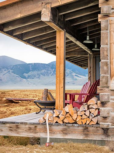 Red Adirondack chairs look out on the Lemhi and Lost River mountains on this Idaho cabin's front porch.