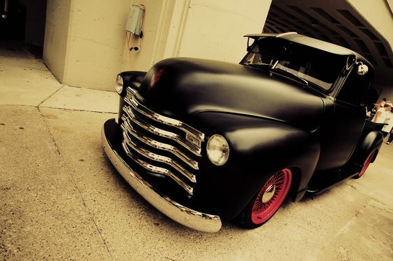 Chevy pickup, satin black with dark red wire wheels, really cool.