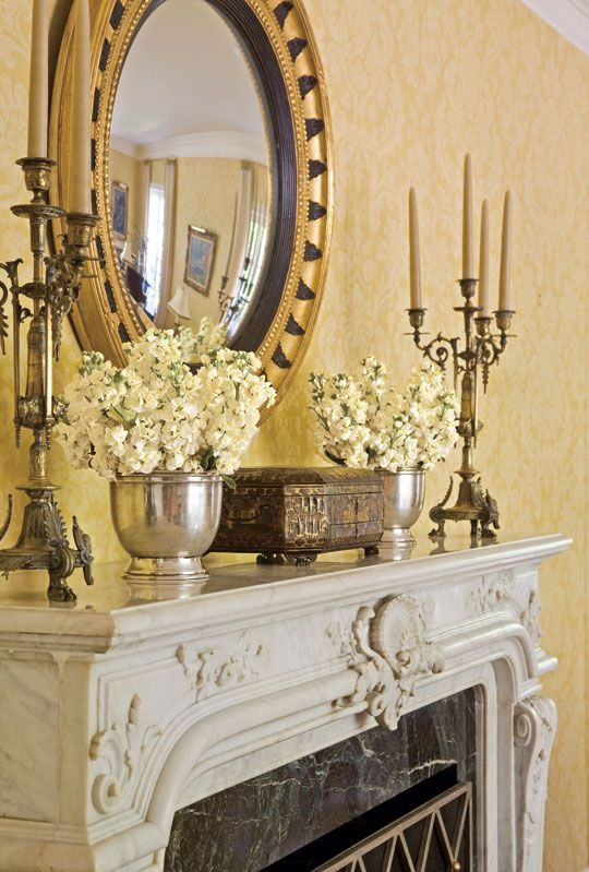 An antique English mirror and 19th-century candlesticks add classic beauty to this mantel - Traditional Home®