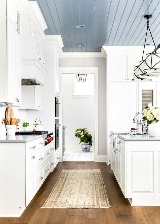 A Grosvenor Linear Triple Pendant Hangs From A Blue Plank Ceiling Over A White Kitchen Island Boasting A Fa Kitchen Ceiling Black Kitchen Faucets Plank Ceiling