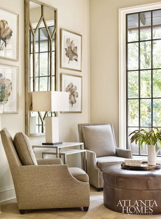 Elegant tone on tone living room with arm chairs and round ottoman. Beautiful Classically Refined Rooms
