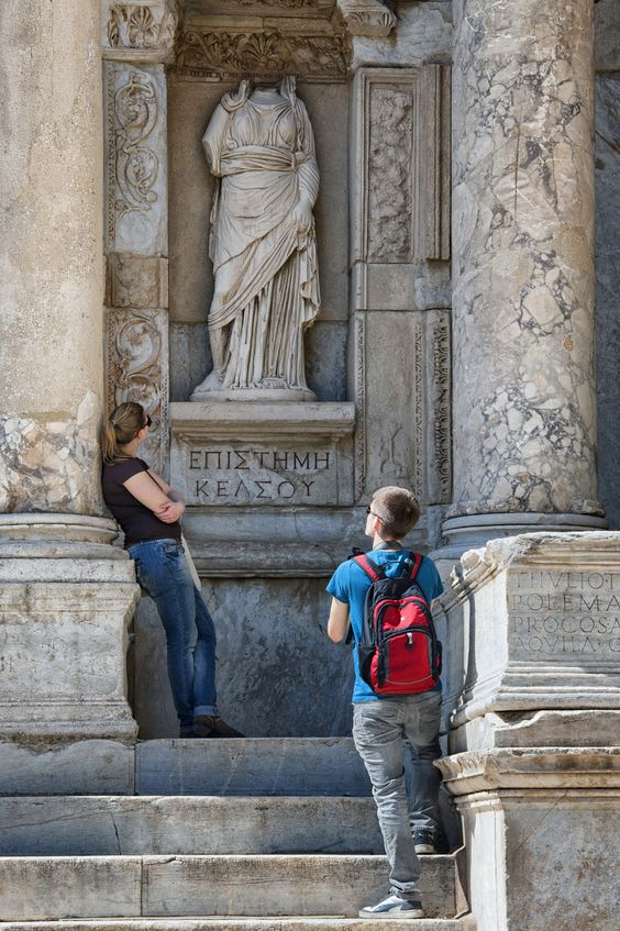 female bond? - two female tourists looking at the headless female marble statue at ephesus library ; an ancient city situated in aegean turkey near izmir and now a unesco World heritage site.