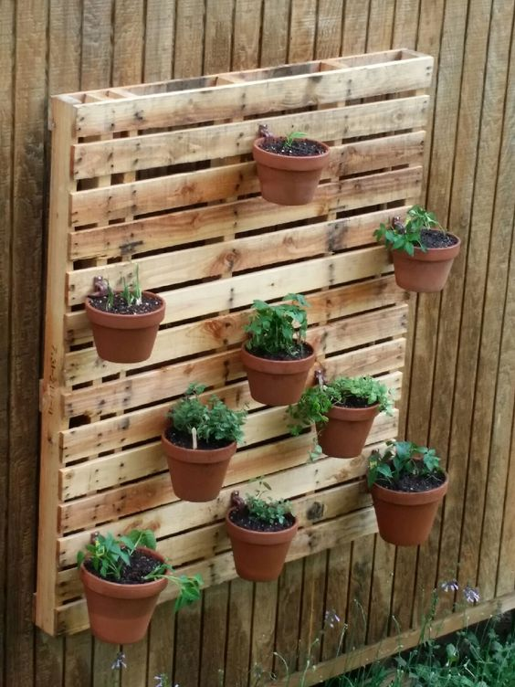 Herb garden on a pallet using hangapot flower pot hangers for How to make plant pots from pallets